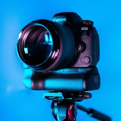 Camera on tripod in front of blue background - look good on camera