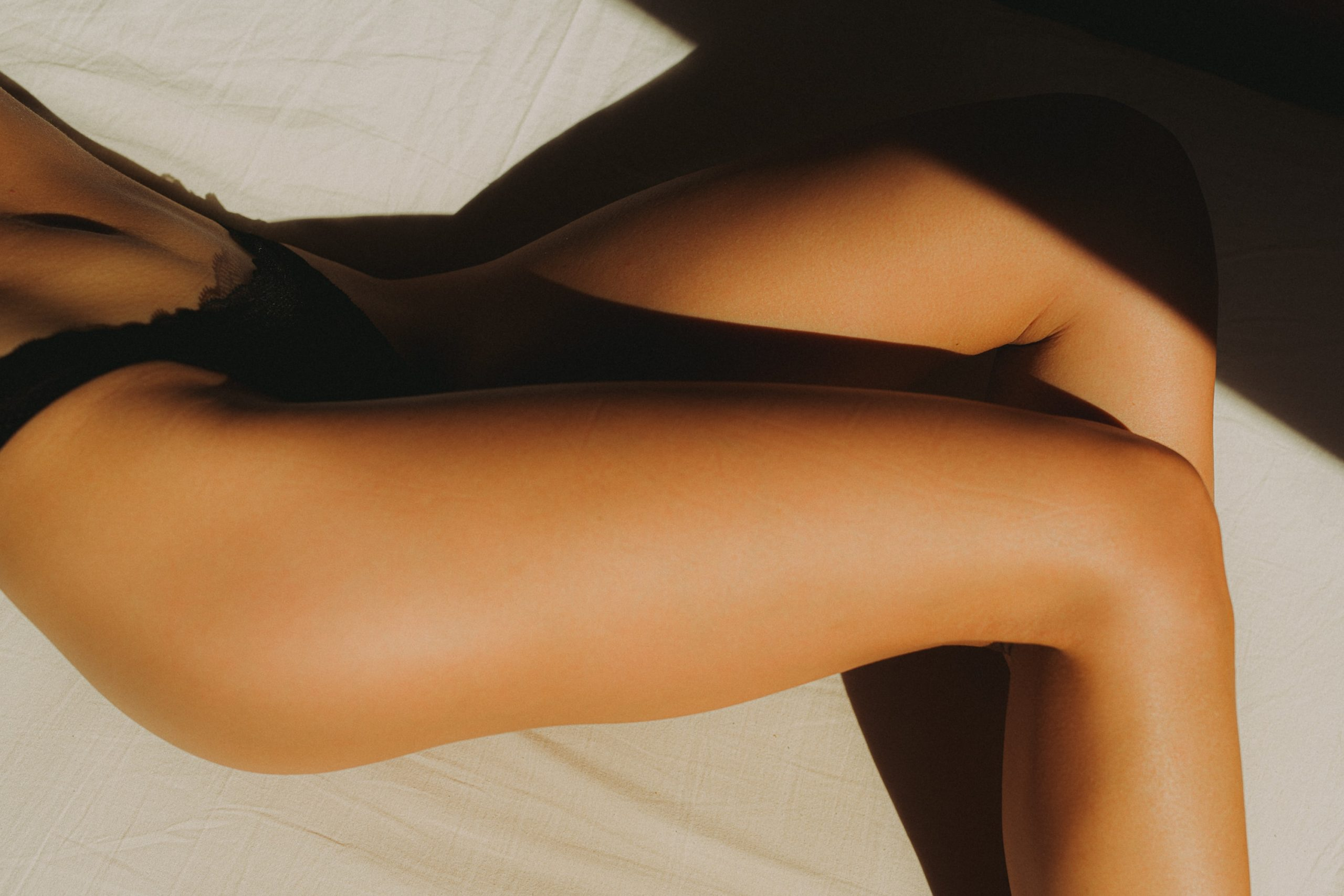 Tanned girl laying on a bed in her underwear